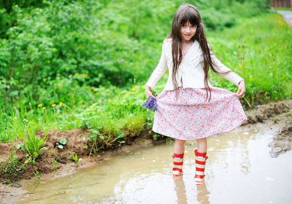 child playing in mud puddle